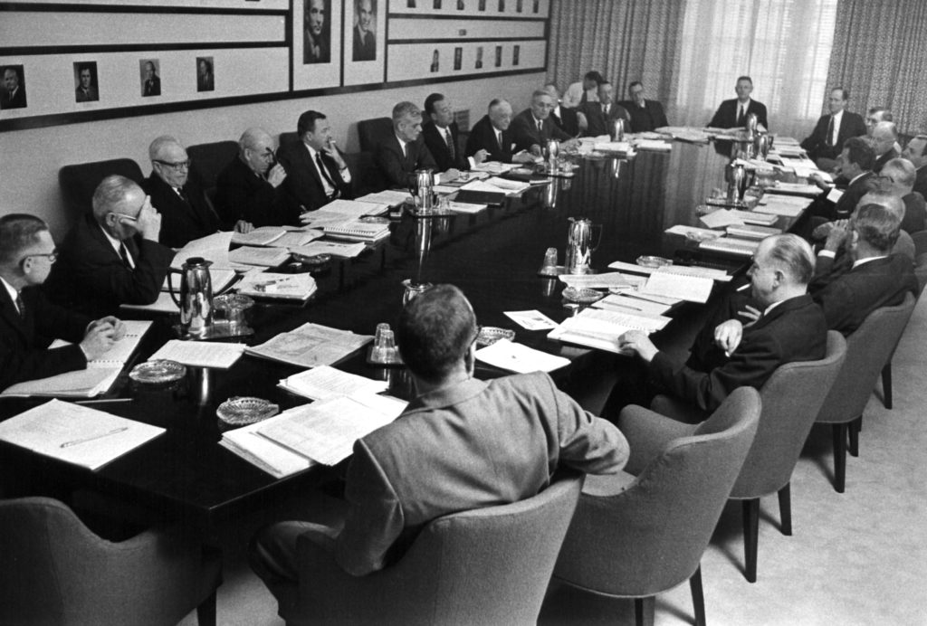 Two dozen men sit around a long oval table, with stacks of paper in front of each one. Some of the men are smoking.