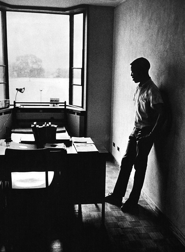 A student participant in the Princeton College Summer Program takes a study break, He is leaning against a wall next to his desk, circa 1960. The program was designed to improve Black education through individual experiences.