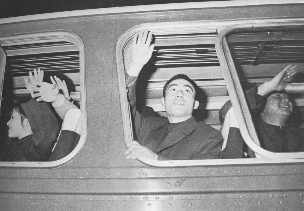 A member of the Chinese table tennis team waves out of a tour bus window