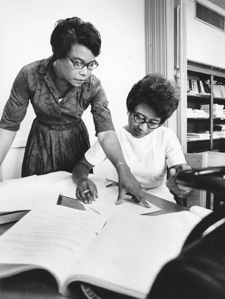 To women study books and papers in a library, they are from the business school at Texas Southern University