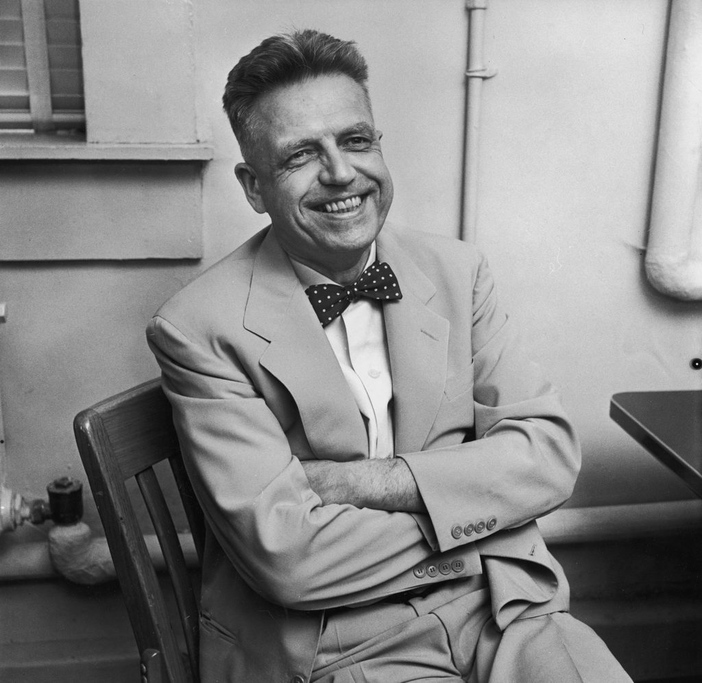 Portrait of Alfred Kinsey wearing a bow tie and sitting at a desk, smiling