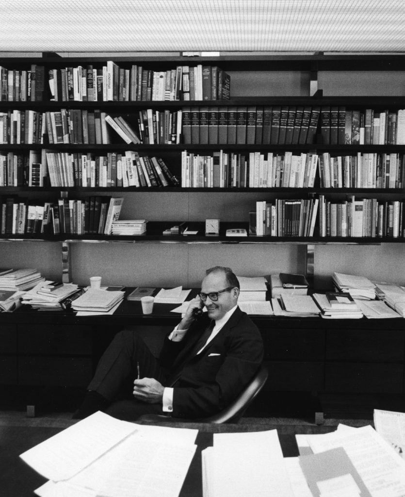 McGeorge Bundy, a white man, is dressed in a suit and sits with books behind him. He holds a telephone receiver and looks busy. Bundy was the Ford Foundation president that promoted a major shift to civil rights funding.