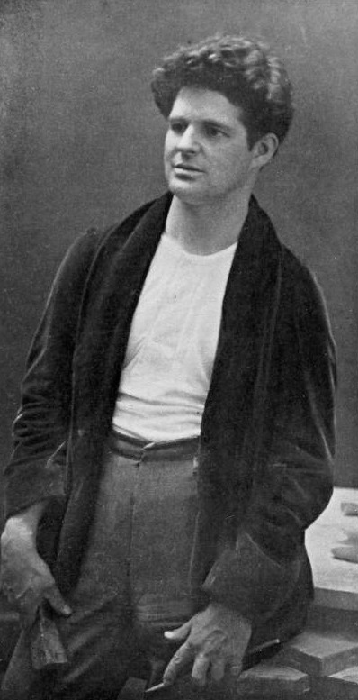 A portrait of George Grey Barnard, dressed in a tee-shirt and dark cardigan, in his studio.