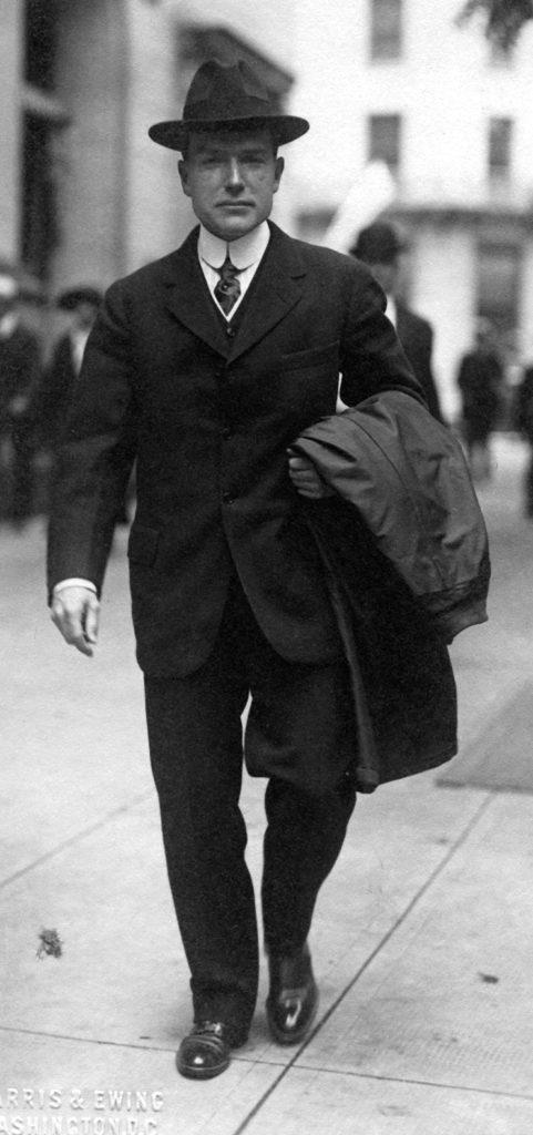 A portrait of John D. Rockefeller, Jr., dressed in a dark three-piece suit and hat, walking on a city sidewalk.