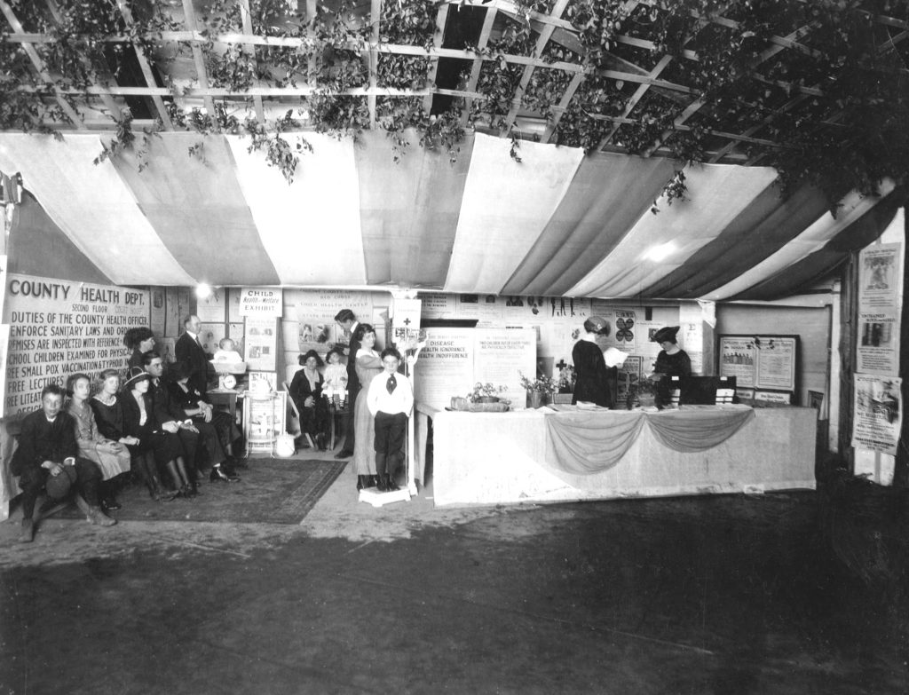 People gathered in a booth at a public health demonstration at a county fair in Texas in the 1900s. They are looking at an exhibit about hookworm disease.