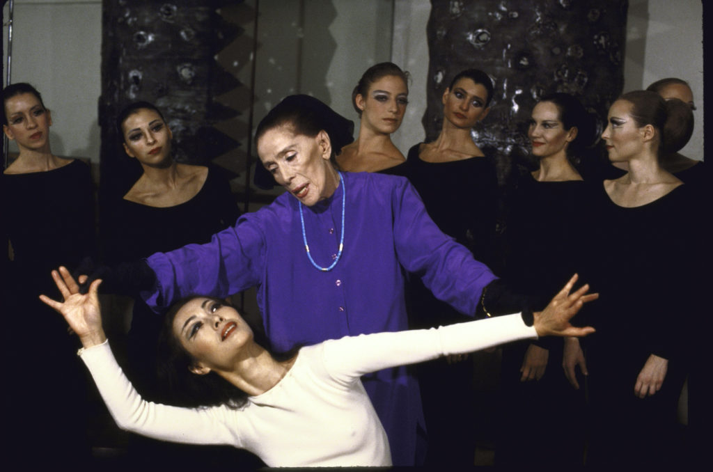 "A photograph of choreographer Martha Graham in action, rehearsing with dancers as they work on her piece, ""Heretic."""
