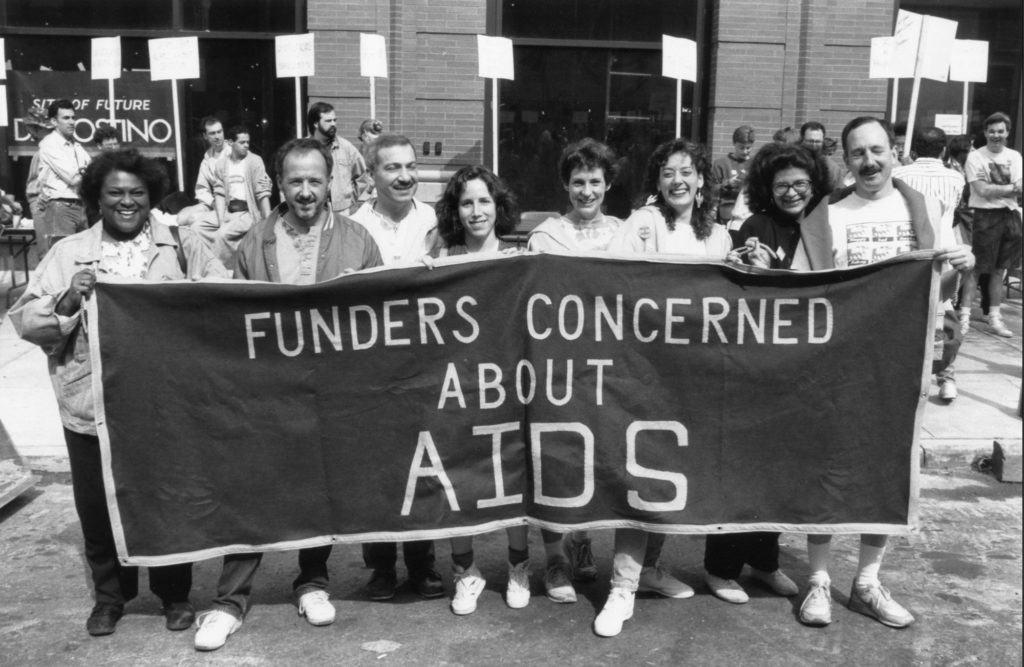 "Eight people of different races and genders hold up a banner that says ""Funders Concerned About AIDS,"" with people marching and holding signs in the background."