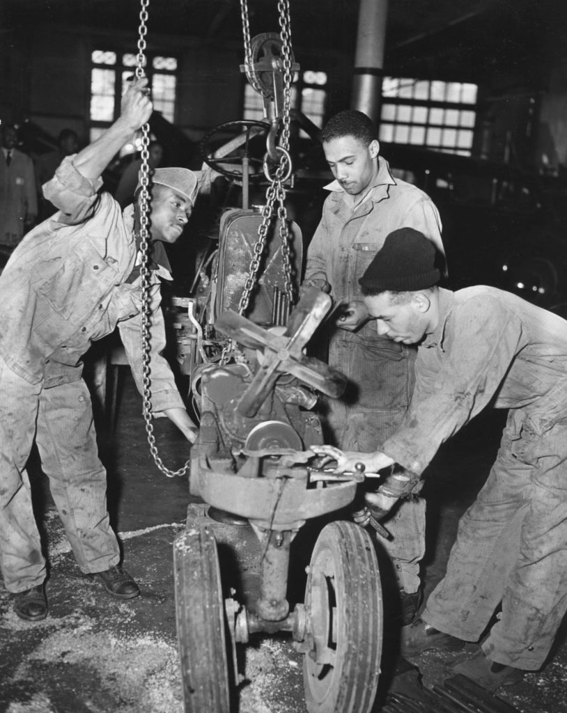 Three black students work on a machine as part of the department of auto diesel mechanics at the Hampton Institute.
