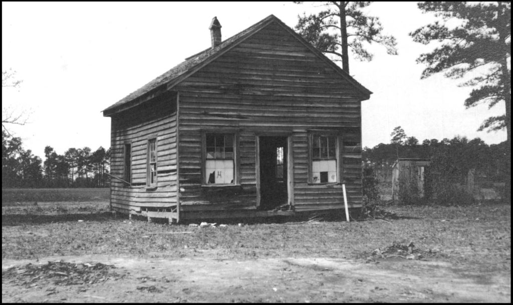 A run-down wooden school building in North Carolina, with windows and parts of the siding are missing. This photograph shows the dire condition of African American schools in the US South in the early twentieth century.