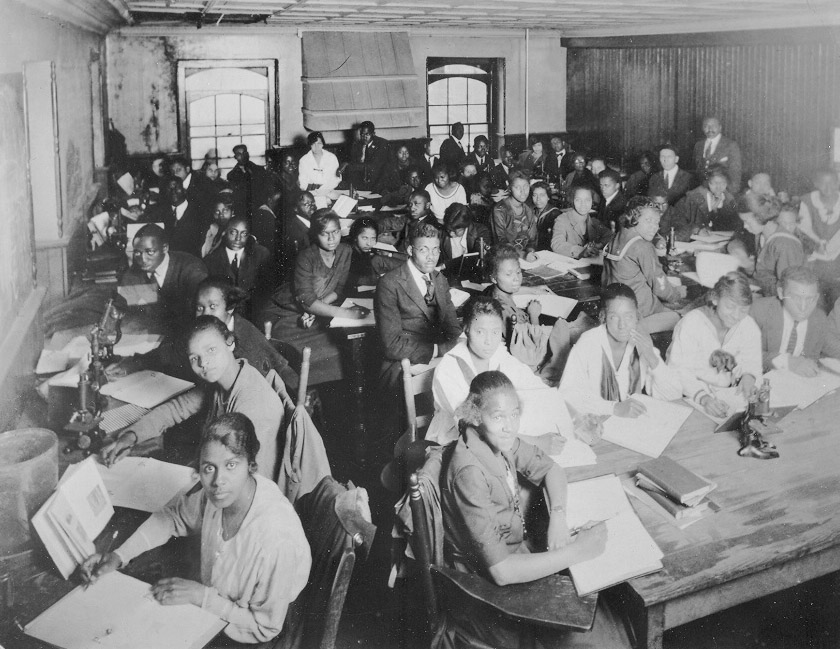 A classroom photo of African American college students, both men and women, at Shaw University in North Carolina. The students sit at tables and are looking at books and taking notes in notebooks. Work in black education spanned elementary schools to colleges and universities.