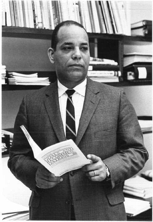 Portrait of Christopher Edley, a Black man in a suit with books behind him. He was the Ford Foundation's first Black program officer, and an early proponent of civil rights funding at the foundation.