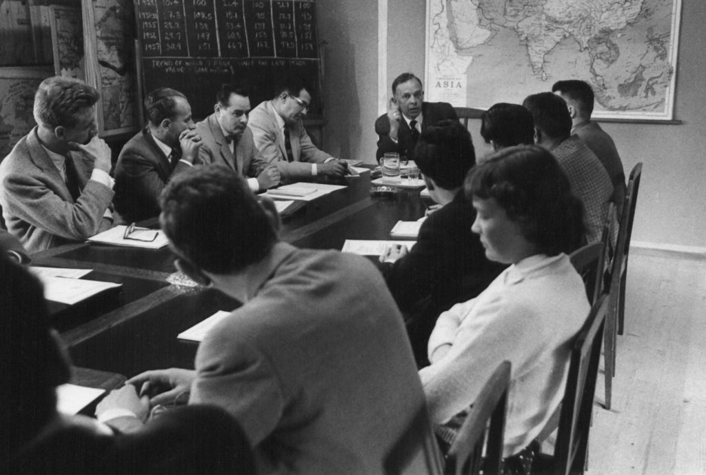 Several men and one woman all in formal dress sit around a table, with a map of Asia and a chalkboard behind them.