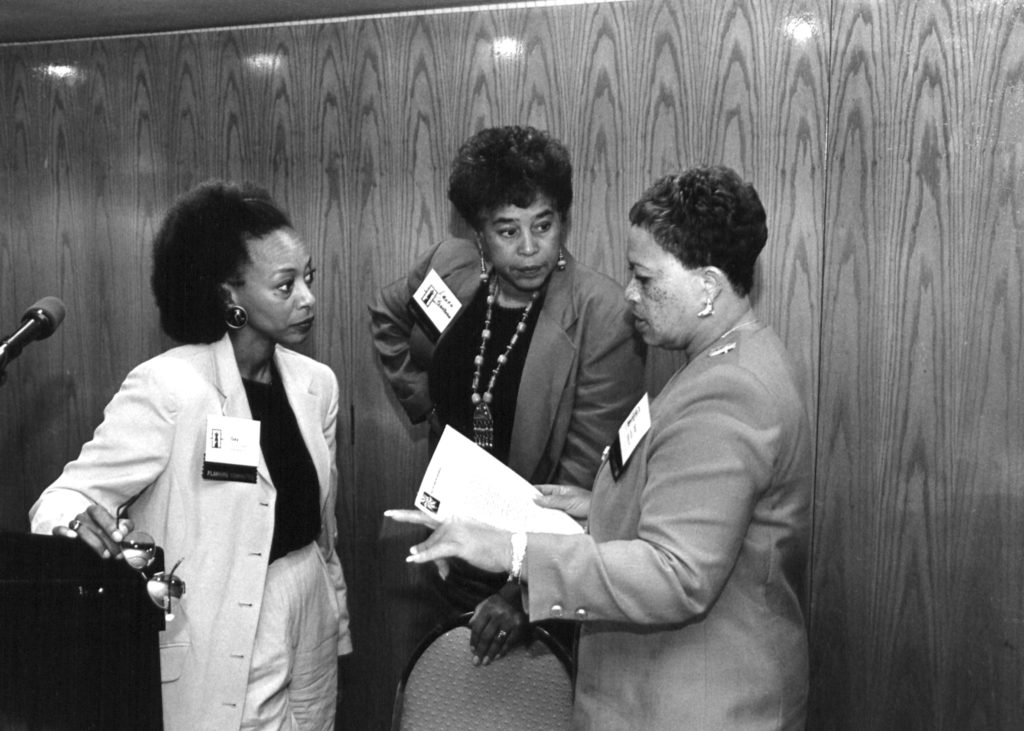 Three Black women lawyers from the Lawyers Committee for Civil Rights Under Law discuss together. One stands at a podium.