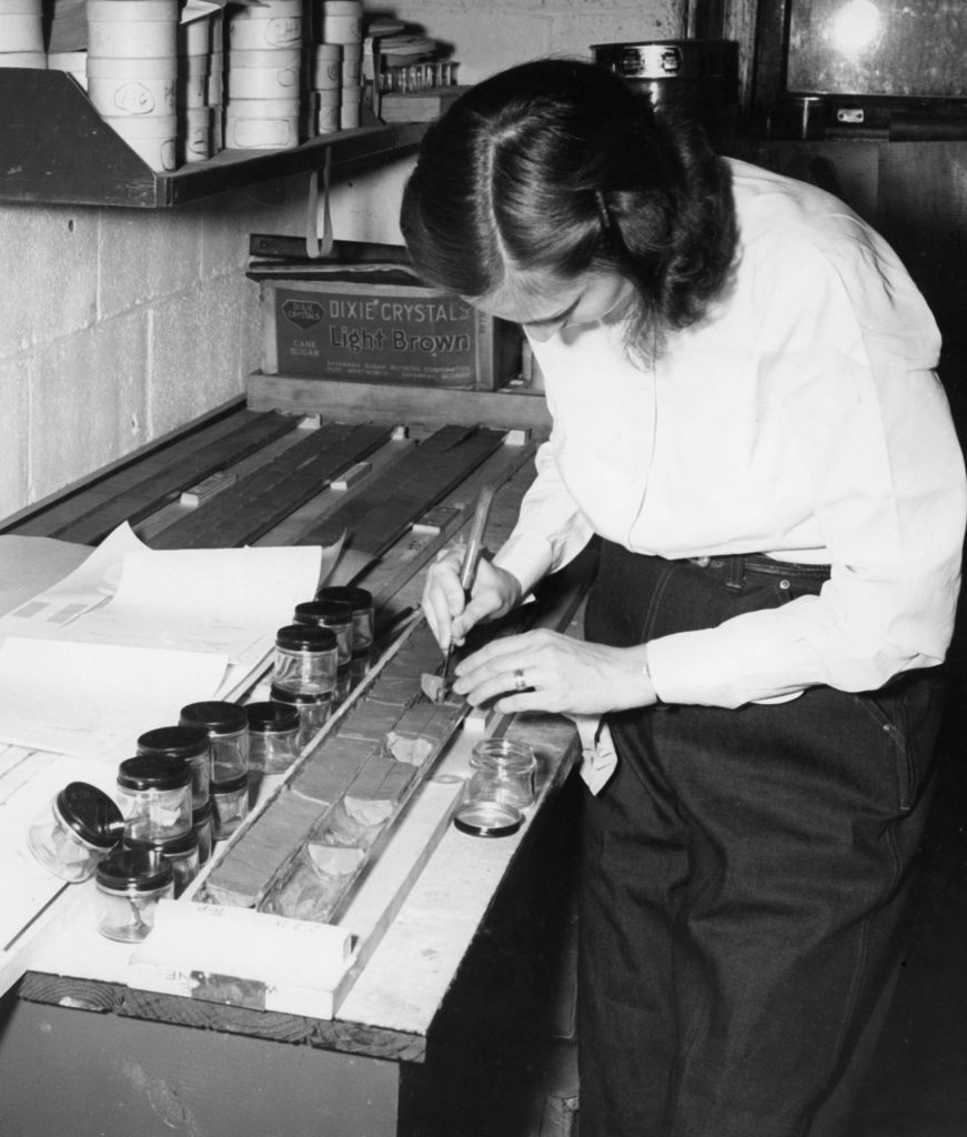 Female oceanographic scientist examines a core sample of sediment collected in glass jars, in her laboratory.