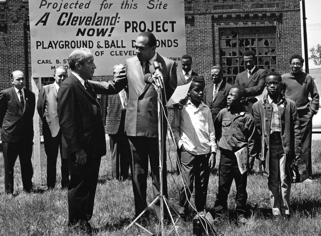 "Cleveland Mayor Carl Stokes, the first Black mayor of Cleveland, stands at a microphone surrounded by Black and white men in suits and Black children. A sign reads ""A Cleveland Now! Project. Playground and Ball Diamonds"""