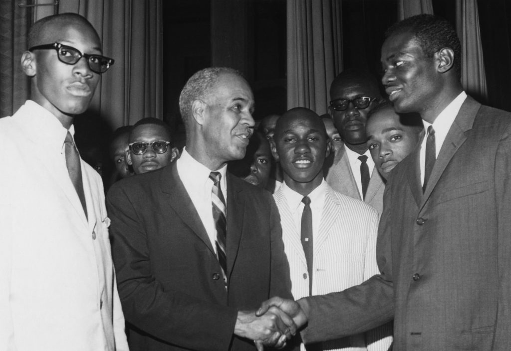 NAACP leader Roy Wilkins shakes hands with another Black man, surrounded by several other Black men. All are wearing suits and ties.