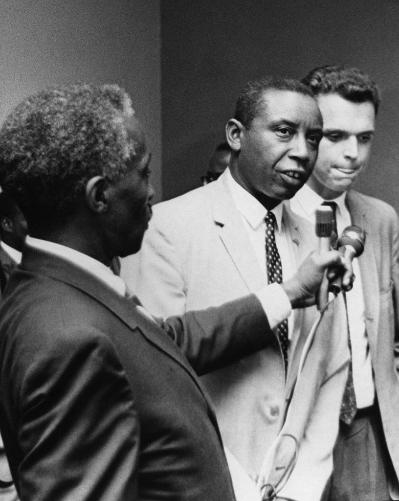 Congress of Racial Equality president Floyd McKissick, a Black man, speaks into a microphone held by another Black man. A white man stands to McKissick's left.