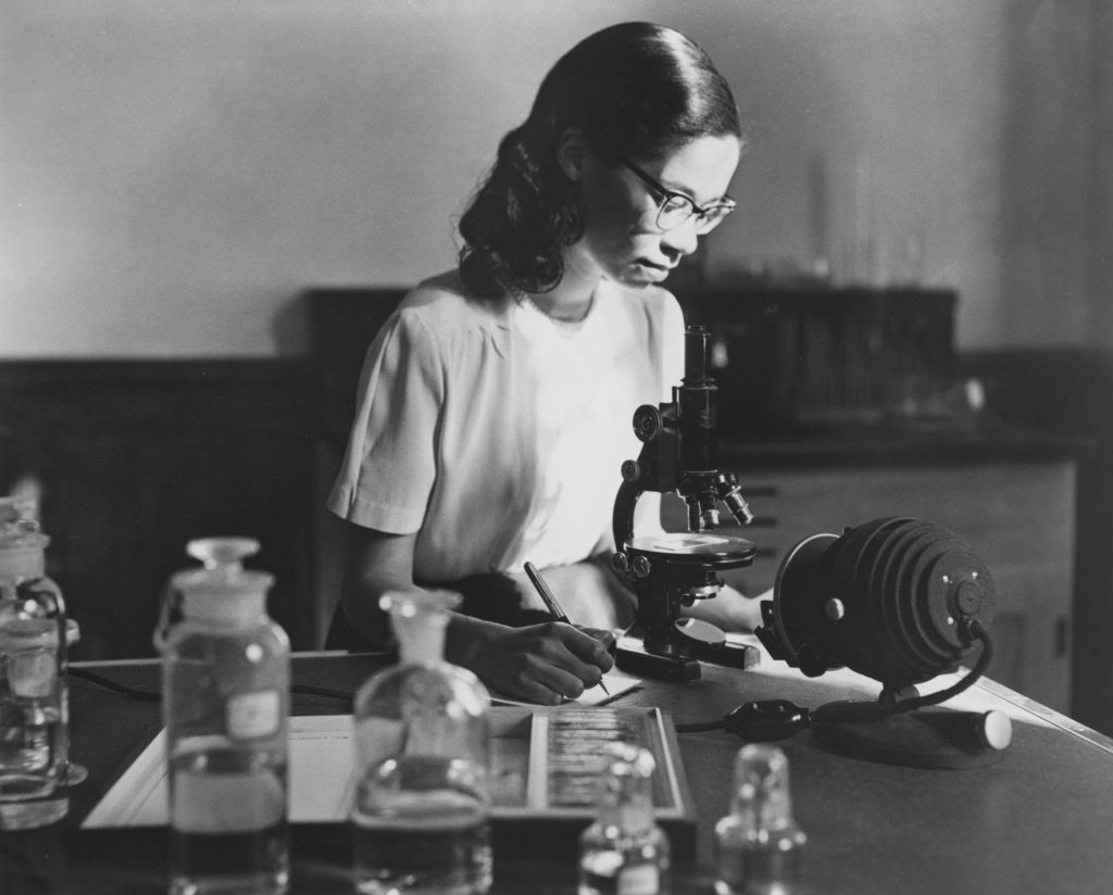 A Black student looks through a microscope. Early foundation grantmaking related to African-Americans was mostly in the field of education.