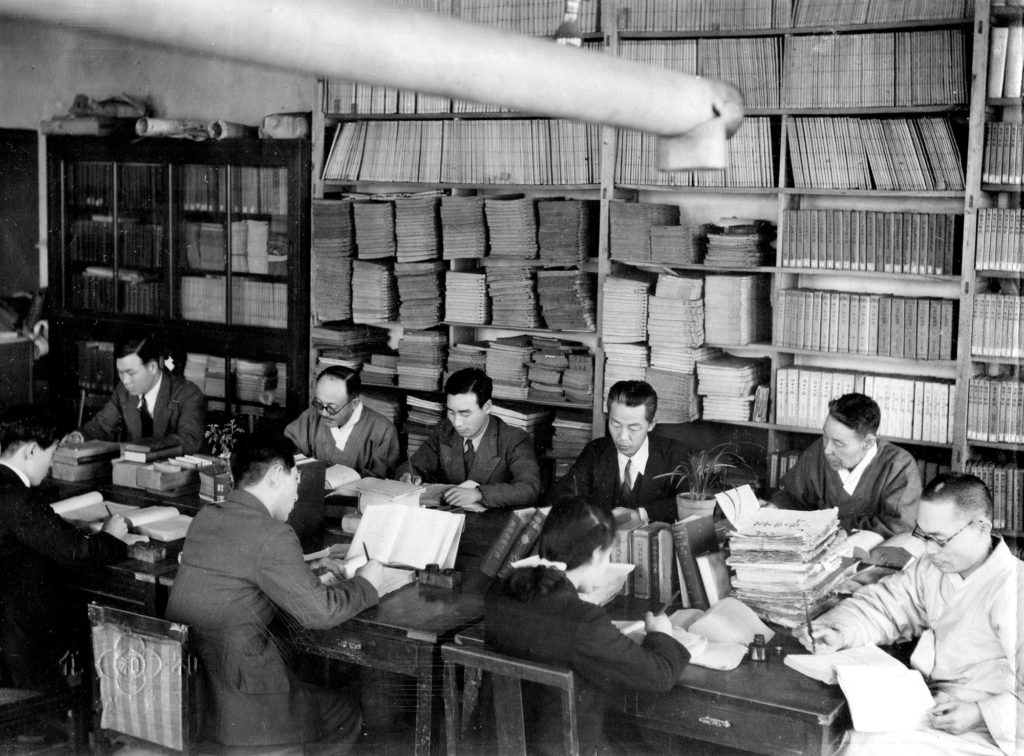 Seven Korean men and one woman work at a large table covered in papers and books. They are working on the Korean (Hangul) Dictionary.
