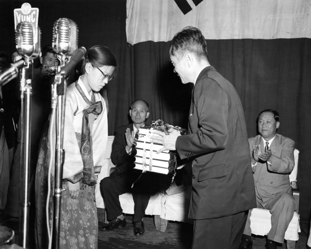A Korean woman in traditional silk robes stands at left while a man at right holds the six-volume Korean (Hangul) dictionary, wrapped in ribbons.