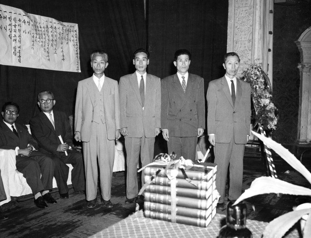 Four Korean men in suits stand behind the six-volume Korean (Hangul) dictionary. They were the scholars who worked on the dictionary.