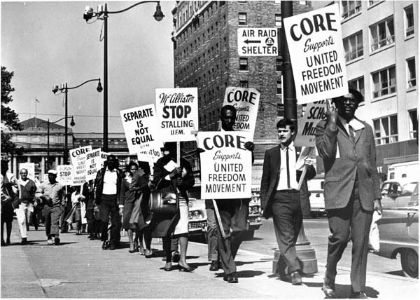 "Black and white men and women in formal dress march in a picket line, with signs reading ""CORE Supports United Freedom Movement."""