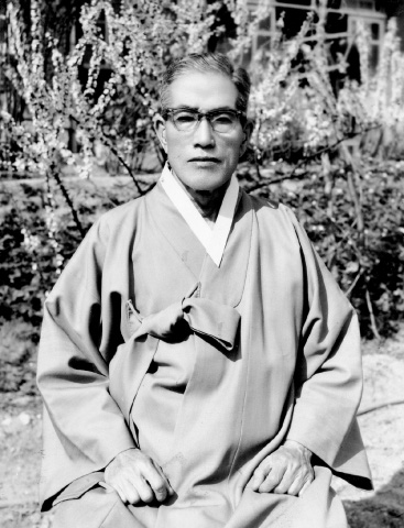 Black and white photograph of Choi Hyon Pai sitting, wearing glasses and traditional Korean robe.